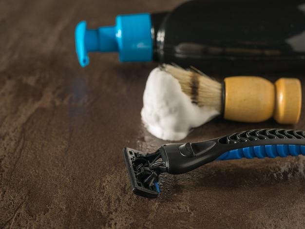 Męska maszynka do golenia, pianka do golenia i mydło w płynie na kamiennym stole. zestaw do pielęgnacji męskiej twarzy. leżał na płasko.