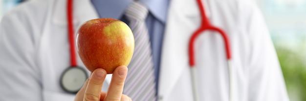 Męska medycyna terapeuta lekarka wręcza mieniu czerwonego świeżego dojrzałego jabłka