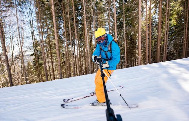 Męska narciarka bierze selfie obrazek używać selfie kij podczas gdy jechać na nartach w dół stoku w górach przy zima ośrodkiem narciarskim