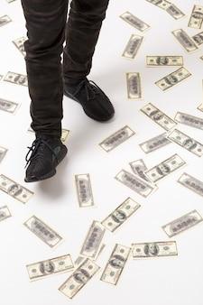 Męska noga nadepnęła na studolarowy banknot na podłodze dużo pieniędzy