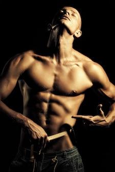 Męska pielęgnacja leczy. zbliżenie młodego nagiego mężczyzny w dżinsach z seksualnym silnym muskularnym pięknym opalonym ciałem pokazującym palec na żółtej taśmie mierniczej okrągłej talii stojącej na czarnym tle, obraz pionowy