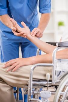 Męska pielęgniarka bierze puls starszy pacjent przy szpitalem.