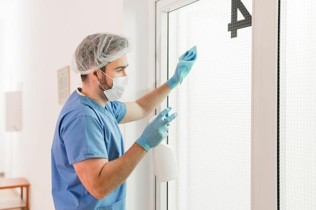 Męska pielęgniarka dezynfekuje okno przy szpitalem