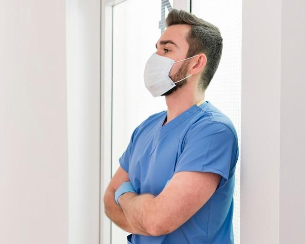 Męska pielęgniarka jest ubranym rękawiczki i maskę