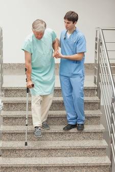Męska pielęgniarka pomaga pacjenta na schodach