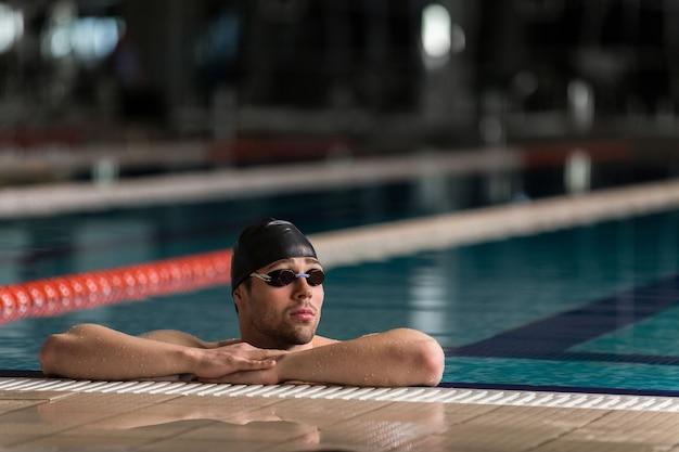Męska pływaczka jest ubranym gogle i pływackiej nakrętki odpoczywać