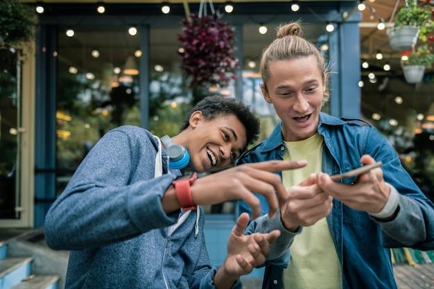 Męska przyjaźń. szczęśliwi młodzi mężczyźni grający z nowoczesnym gadżetem podczas wspólnej zabawy