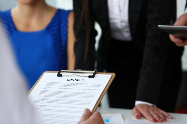 Męska ręka chwyta kontrakta forma obcięta ochraniacza zbliżenie. uderza tranzakcja dla zysku urzędniczego motywaci zrzeszeniowej decyzi notariusza wykonawczego sprzedaży projekta ubezpieczeniowego agenta zakupu pojęcie