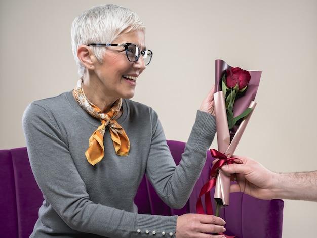 Męska ręka daje czerwoną różę swojej uroczej, szczęśliwej żonie