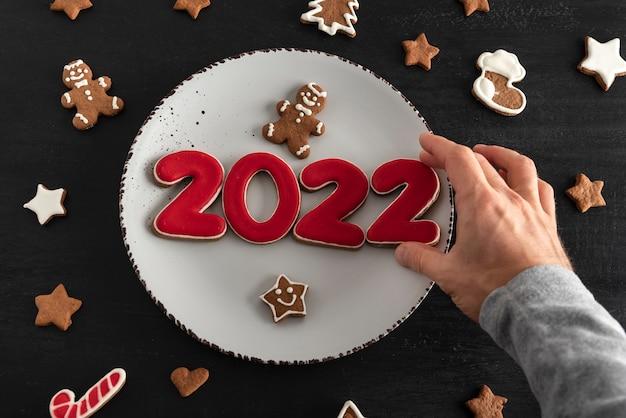 Męska ręka kładzie smaczne glazurowane malowane ciasteczka na białym talerzu: cyfry 2022, gwiazdy i jodła. noworoczna koncepcja żywności