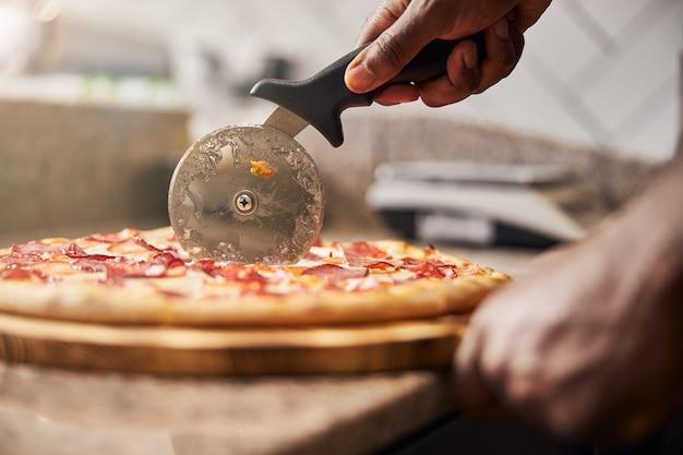 Męska ręka krojąca świeżo upieczoną pizzę za pomocą okrągłego koła tnącego