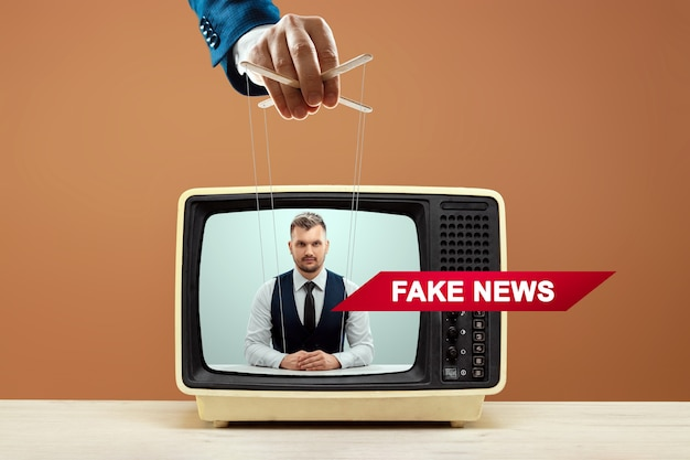 Męska ręka lalkarza manipuluje spikerem, fałszywymi wiadomościami, oszustwem. pojęcie rządu cieni, spisek światowy, manipulacja, kontrola, tabloidy.