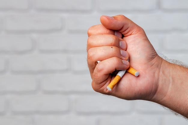 Męska ręka łamie papierosy rzucając zły nawyk