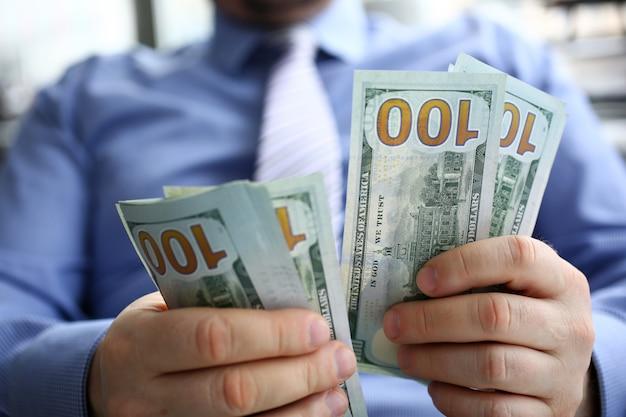Męska ręka liczy sto dolarowych rachunków zbliżeń