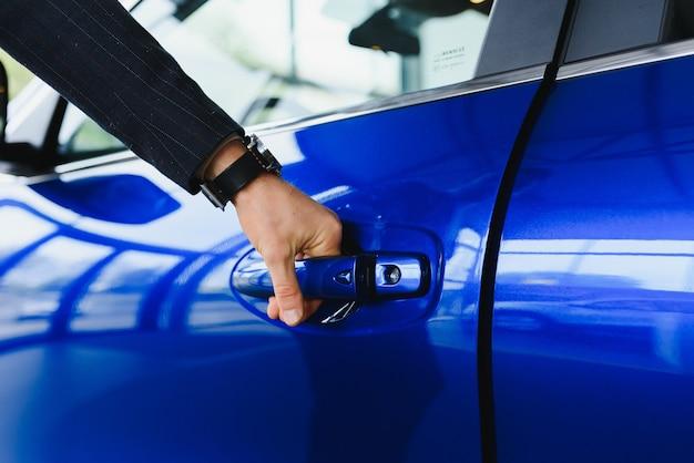 Męska ręka na dźwigni zmiany biegów w samochodzie
