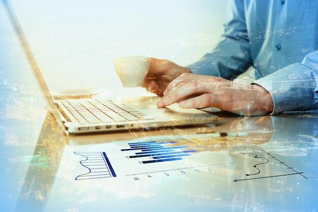 Męska ręka na klawiaturze i ręka z kawą na powierzchni stołu z długopisem