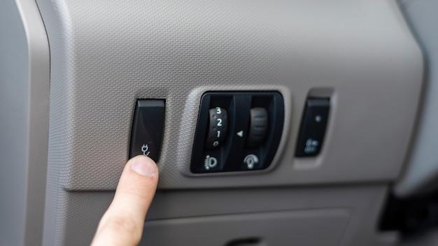 Męska ręka naciskająca przycisk w samochodzie elektrycznym