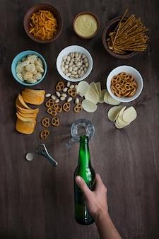 Męska ręka nalewa piwo