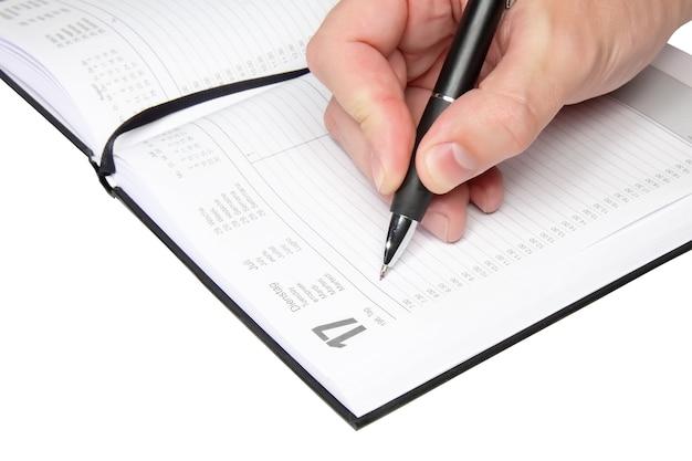 Męska ręka napisz trochę w organizerze. pojedynczo na białym.