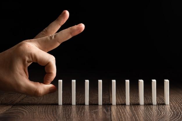 Męska ręka pcha białych domino na brown drewnie