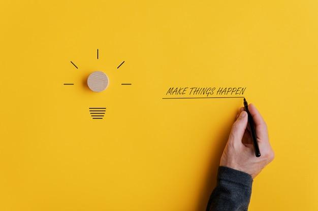 """Męska ręka pisząca znak """"spraw, by coś się stało"""" obok kształtu żarówki na żółtym tle"""