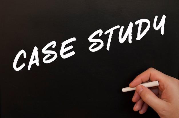 Męska ręka pisze kredą na czarnej tablicy słowa case study