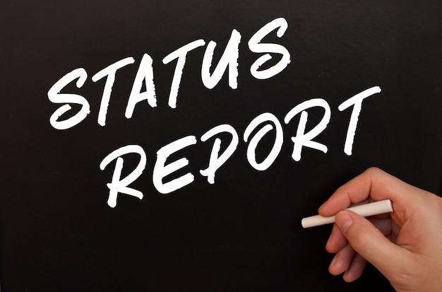 Męska ręka pisze kredą na czarnej tablicy słowa raport statusu