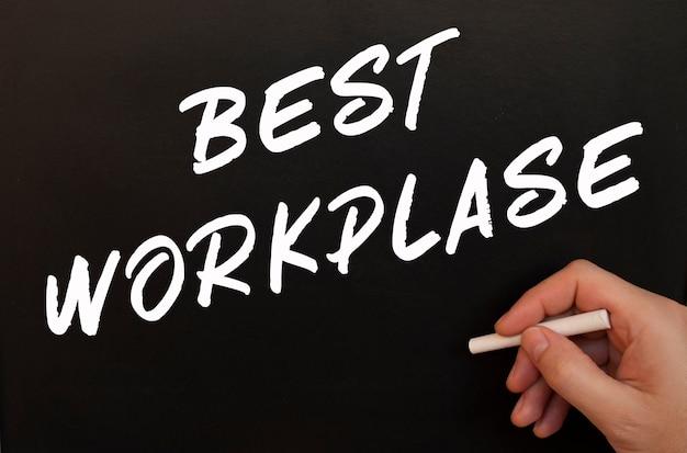 Męska ręka pisze słowa best workplase na czarnej tablicy. narysowany kredą w męskiej dłoni. pomysł na biznes.