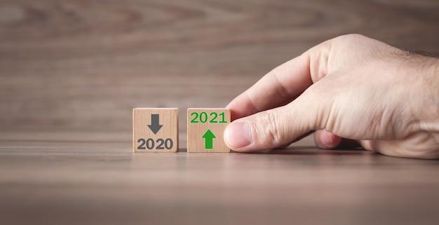 Męska ręka pokazująca 2020 i 2021 na drewnianych kostkach.