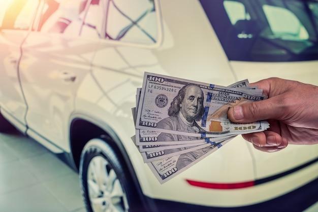 Męska ręka pokazująca dolara za zakup samochodu w autohouse. finanse