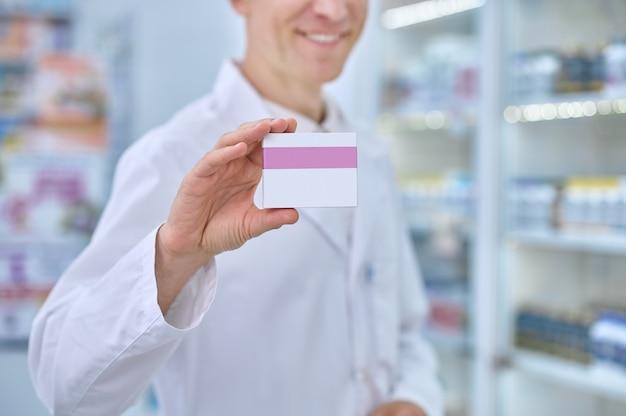 Męska ręka pokazująca opakowanie produktu leczniczego