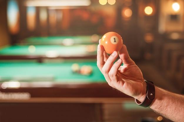 Męska ręka pokazuje bilardową kulę numer osiem.
