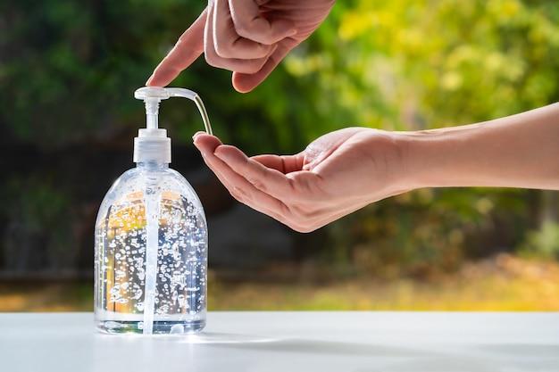 Męska ręka pompuje antyseptyczny żel do rąk z przezroczystej butelki na drugą rękę