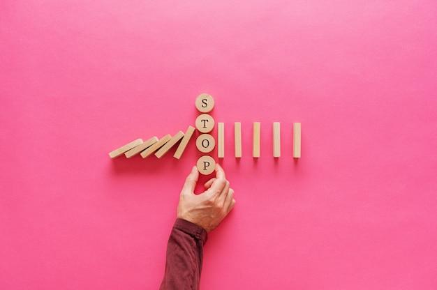 Męska ręka przerywająca spadające domino