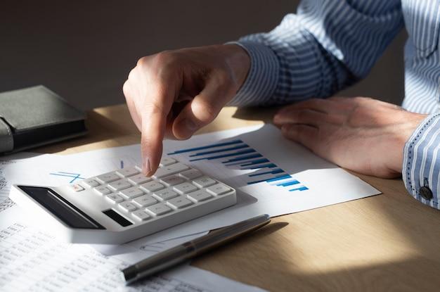 Męska ręka przy biurku z dokumentem finansowym z wykresem trendu wzrostowego, wykonywaniem obliczeń, przygotowywaniem raportu. pojęcie wzrostu gospodarczego.