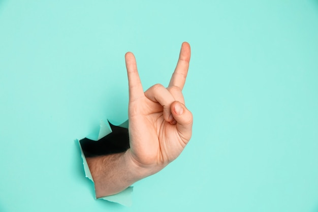Męska ręka robi rock and rolla gest, impreza, koza na niebieskim tle