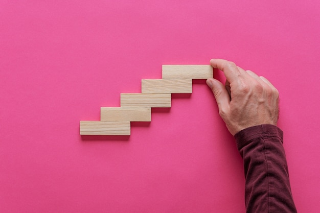 Męska ręka robi schody jak struktura drewnianych kołków. koncepcyjny obraz wzrostu i rozwoju.
