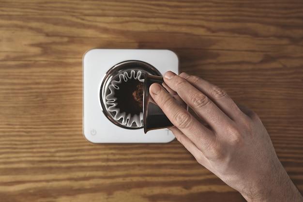 Męska ręka rozlewa paloną mieloną kawę z metalowej, nierdzewnej filiżanki do chromowanego przelewowego ekspresu do kawy, aby przygotować filtrowaną kawę w kawiarni
