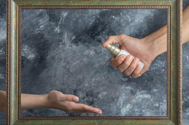 Męska ręka rozpyla etanol do kobiety w środku kadru.