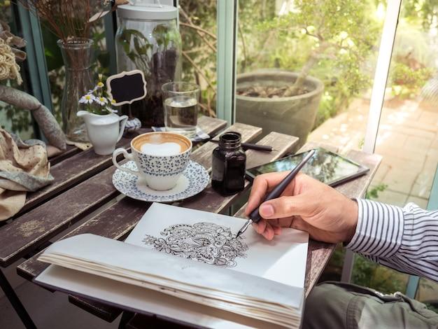 Męska ręka rysuje doodle kreskową sztukę na papierze z kawą i pastylką