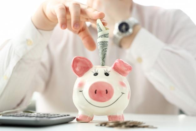 Męska ręka stawia papierowe pieniądze w śmiesznym gniazdeczka skarbonka