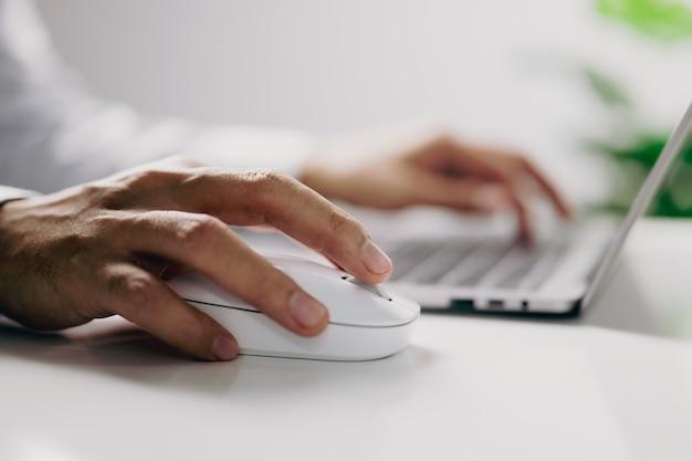 Męska ręka trzyma białą mysz komputerową z laptopem w biurze