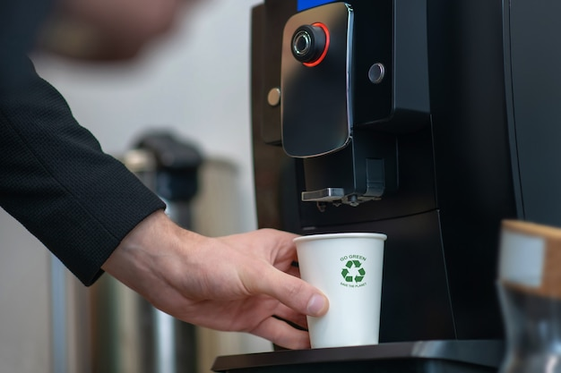 Męska ręka trzyma biały papierowy kubek z zielonym znakiem w pobliżu stojaka na maszynie do napojów