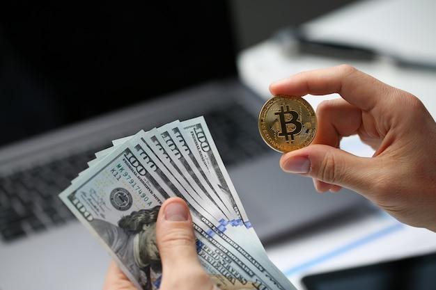 Męska ręka trzyma bitcoin i dolarową monetę