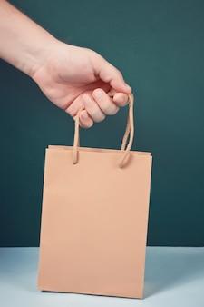 Męska ręka trzyma brown papierową torbę z uchwytami.