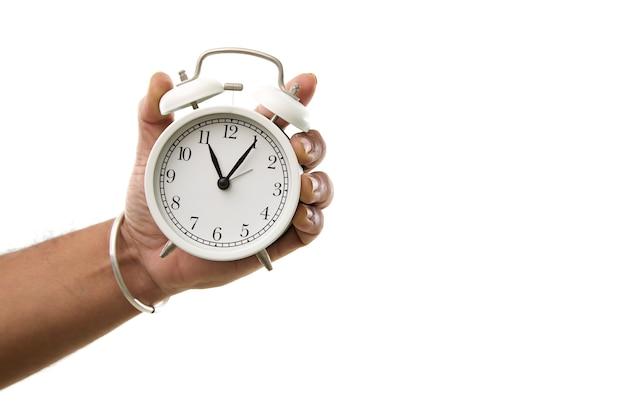 Męska ręka trzyma budzik na białej ścianie