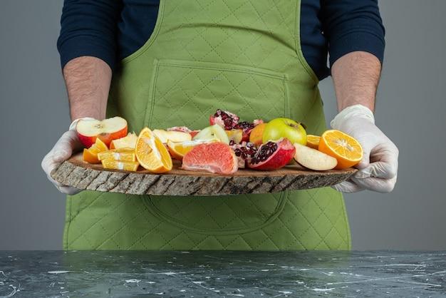 Męska ręka trzyma bukiet świeżych owoców na marmurowym stole.