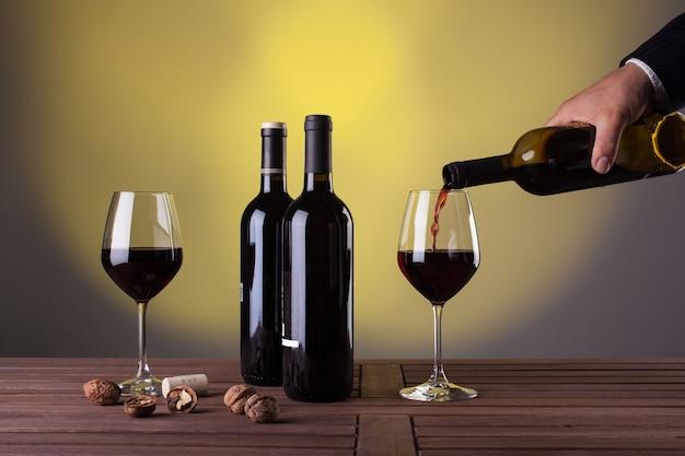 Męska ręka trzyma butelkę czerwonego wina i wlewając do kieliszka