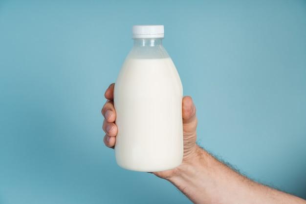 Męska ręka trzyma butelkę mleka na niebieskiej ścianie