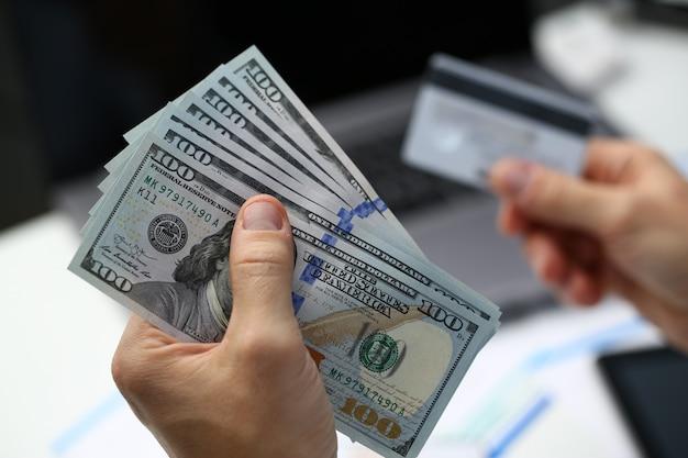 Męska ręka trzyma dolarowych banknoty i plastikową bank kartę w ręki zbliżeniu. wypłacaj pieniądze zarobione w internecie na swoje konta za pośrednictwem koncepcji płatności terminala płatniczego za kliknięcie.